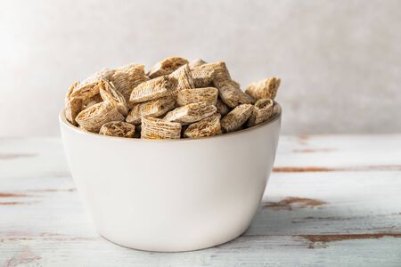 Healthy breakfast in the bowl such as bitesize shredded wheat on light background