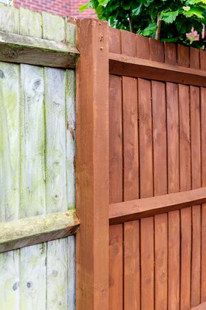Painting old wooden fence with a brown paint