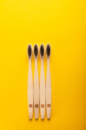 A family set of four wooden bamboo toothbrushes. Save the planet or no plastic concept. Top view, flatlay, copy space