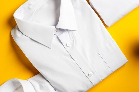 Flat lay with back to school concept, school uniform such as white shirts on bright yellow background Stockfoto