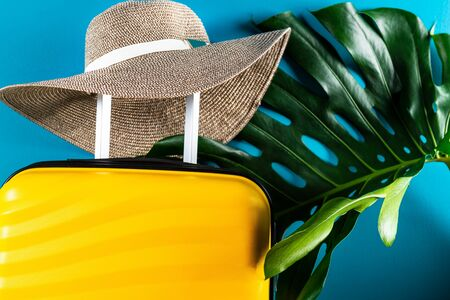 Bright and stylish cabin size suitcase with straw hat against dark blue background. Easy travel with little baggage concept. Copy space.