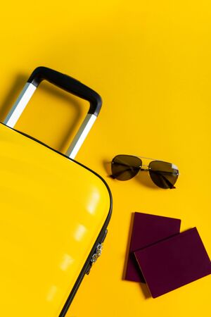 Bright and stylish cabin size suitcase with straw hat, sunscreen and passports flat lay. Easy travel with little baggage concept. Copy space.