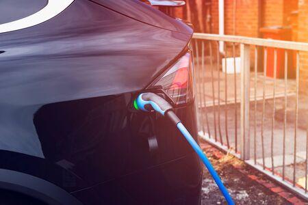 Charging modern electric car on the street car parking, sun flare effect Stock fotó - 127536977