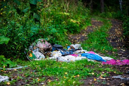 Big rubbish dump in the forest near the road. Say no to plastic concept. People are creating environmental damage