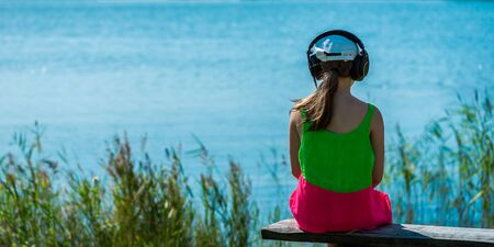 Young girl is relaxing on the bench near the sea, she is listening to the music and is enjoying warm summer day