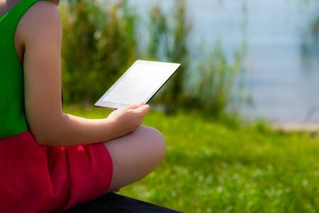 Young girl is reading ebook on the bench near the sea, also she is enjoying warm summer day