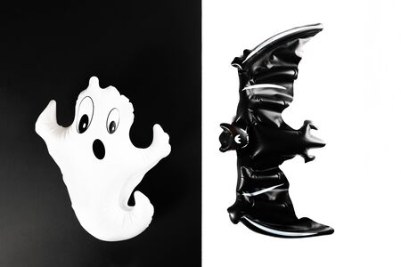 Inflatable bat and ghost as Halloween party decoration concept, black and white background, top view, copy space