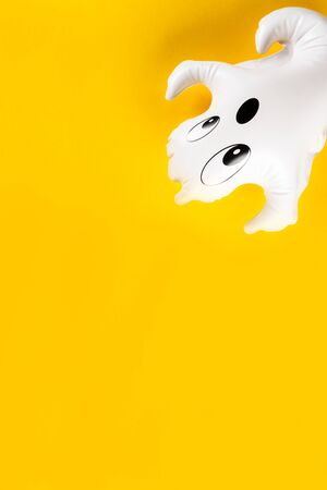 Inflatable white ghost as Halloween party decoration symbol on bright yellow background, top view, copy space