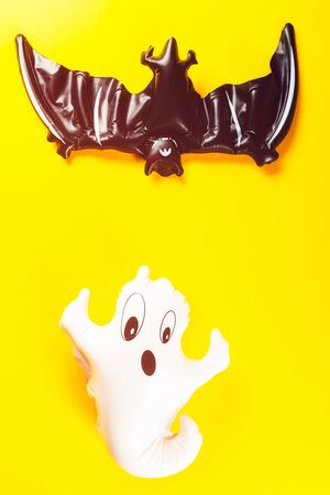 Inflatable white ghost and black bat as Halloween party decoration symbols on bright yellow background, top view, copy space