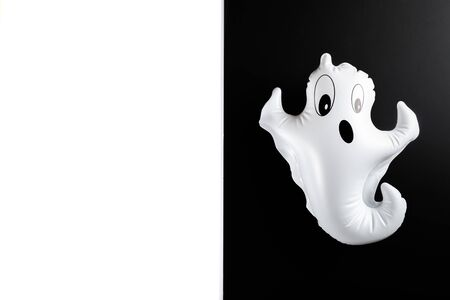 Inflatable white ghost as Halloween party decoration concept, black and white background, top view, copy space