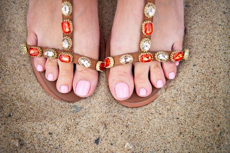 Beautiful feet of young lady with perfect pedicure and pink nails in trendy sandals