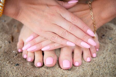Young lady is showing her light pink manicure and pedicure nails on sandy beach backgroung, copy space. Summer holidays concept