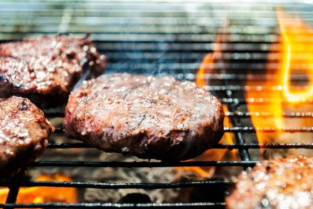 Beef burgers are cooking on the grill with open flames Stock fotó