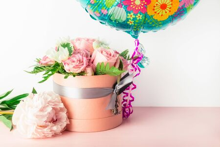 Beautiful and tender bouquet of flowers in the hat box with balloon nearby, nice present concept