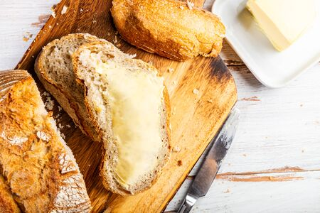 Freshly baked bread with butter on wooden cutting board