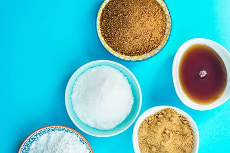Different Kinds of Sugar and Sweeteners in the Bowls, such as coconut, pure cane, icing, maple syrup, dark brown soft sugar, honey, demerara cubes Stock fotó