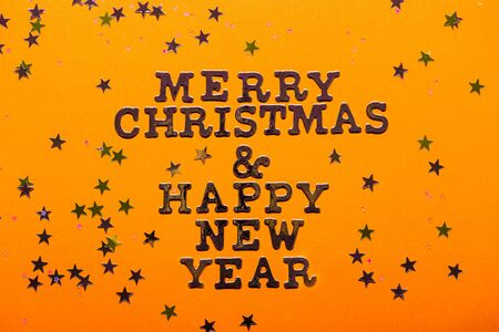 Merry Christmas and Happy New Year letters with stars on bright yellow background Stock fotó
