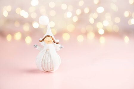 Close up of tiny pretty Angel dresses in white winter cloth, Christmas postcard concept, feminine pink background, copyspace
