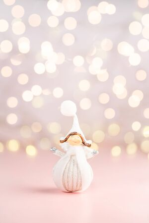 Close up of tiny pretty Angel dresses in white winter cloth, xmas postcard concept, feminine pink background, copyspace Zdjęcie Seryjne