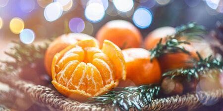 Clementinas frescas o mandarinas en la canasta en la mesa de madera marrón con luces de Navidad y ramas de árboles, banner Foto de archivo