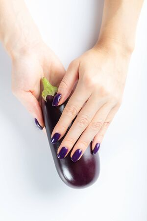 Stylish trendy purple female manicure. Young woman hands are holding augbergine, isolated background 写真素材 - 133623767