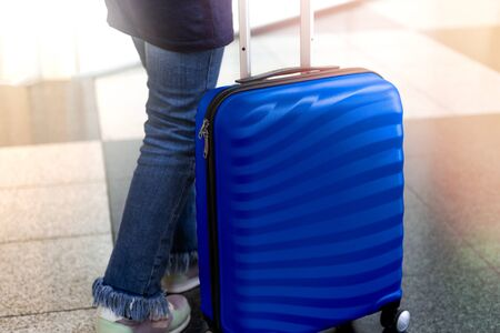 Girl is in the airport with bright and stylish blue cabin size suitcase as holiday concept. Easy travel with little baggage