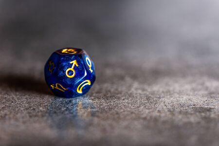 Blue Astrology Dice with symbol of the planet Mars on dark grey background Stock Photo