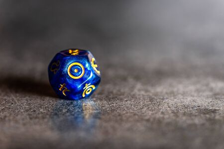 Blue Astrology Dice with symbol of the Sun on grey background