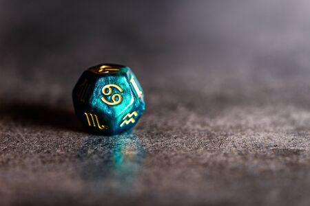 Astrology Dice with zodiac symbol of Cancer Jun 21 - Jul 22 on dark background