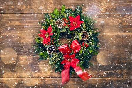 Amazing Christmas wreath with big red bow, Red Christmas Poinsettia flowers and Holly Berries on wooden background, Xmas celebration concept