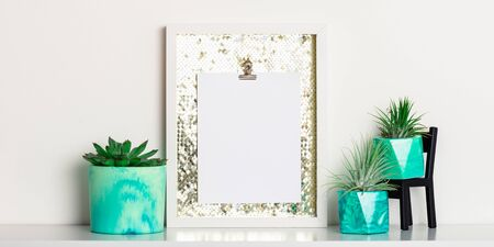 Lifestyle home decoration with frame and place for text. Marbled geometric succulent planters with beautiful tiny succulent plants on white shelf against white wall. Banner size