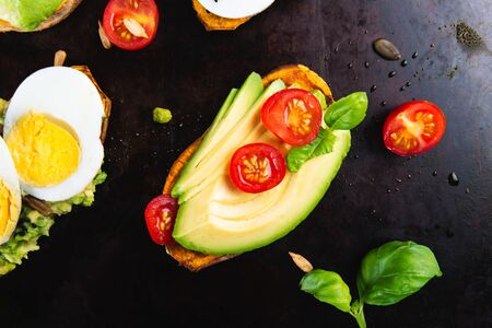 Sweet potato toasts with avocado, boiled eggs, tomatoes and sesame seeds on dark background. Healthy meal concept. Clean eating, Pescetarian food, top view