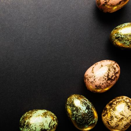 Natural Golden Speckled Easter Eggs of pastel colors on black background. Happy Easter card concept, minimalistic design, copy space Zdjęcie Seryjne