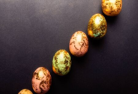 Natural Golden Speckled Easter Eggs of pastel colors on black background. Happy Easter card concept, minimalistic design, copy space Stock Photo