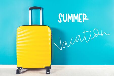 Summer Vacation words. Bright and stylish cabin size suitcase against blue background. Easy travel with little baggage concept. Copy space. Archivio Fotografico