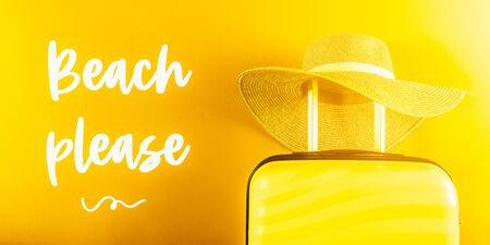 Beach Please words. Bright and stylish cabin size suitcase with straw hat against bright yellow background. Easy travel with little baggage concept. Banner size Archivio Fotografico