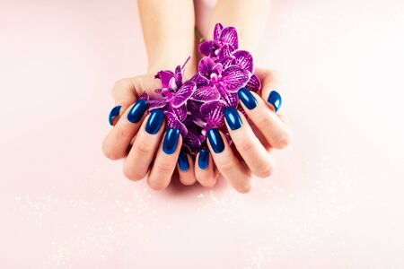 Stylish trendy blue female manicure. Woman hands are holding orchid flowers