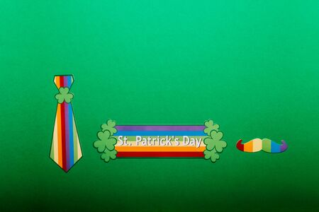 Different photo booth props for St Patricks Day party, top view, green background, rainbow LGBT flag
