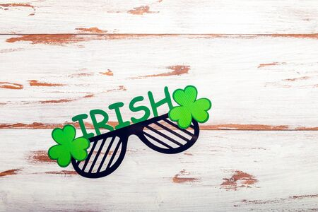 Different photo booth props for St Patricks Day party, top view, rustic wooden background