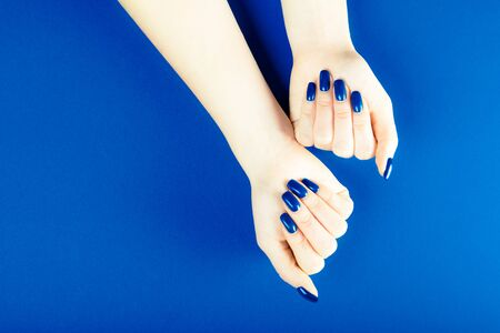 Stylish trendy blue female manicure. Young woman hands on the blue background