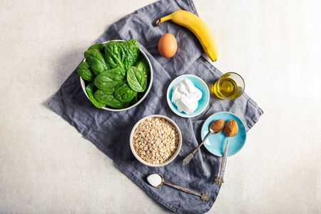 Ingredients for healthy green pancakes such as spinach, coconut milk, banana, egg and oats. Vegetarian and gluten free breakfast