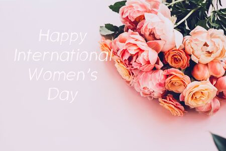 Happy International Womens Day words. Fresh bunch of pink peonies and roses on pink background. Card Concept, pastel colors, close up image, copy space
