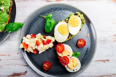 Sweet potato toasts with avocado, boiled eggs, tomatoes and sesame seeds on white rustic background. Healthy meal concept. Clean eating, Pescetarian food, top view