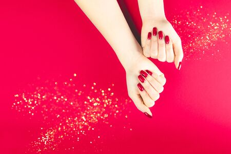 Stylish trendy red female manicure. Young woman hands on the red background Reklamní fotografie