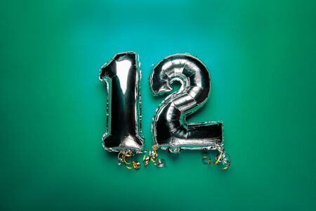 Silver Number Balloons 12 on green background. Holiday Party Decoration or postcard concept with top view Reklamní fotografie