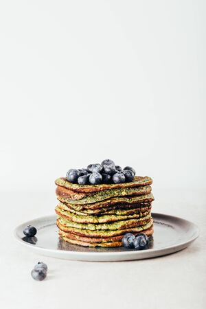Healthy easy blender green pancakes made from spinach, coconut milk, banana and oats with blueberries. Vegetarian and gluten free breakfast Reklamní fotografie