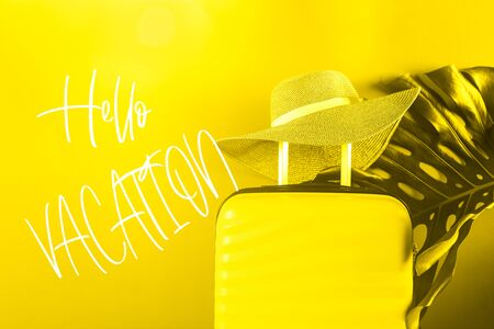 Hello Vacation phrase. Bright and stylish cabin size suitcase with straw hat against bright yellow background. Easy travel with little baggage concept.