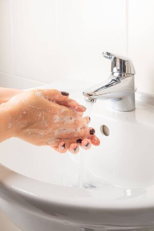 Woman is washing hands with soap under running water for 20 seconds. The main advice to stay healthy during Coronavirus Covid 19 pandemic
