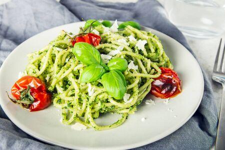 Pasta spaghetti with homemade pesto sauce, roasted tomatoes and fresh basil leaves, vegetarian food Stockfoto