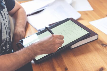 Young university professor is doing online lecture for his students from home during lockdown. He is using 2 in 1 convertible laptop and is writing math formulas with stylus pen